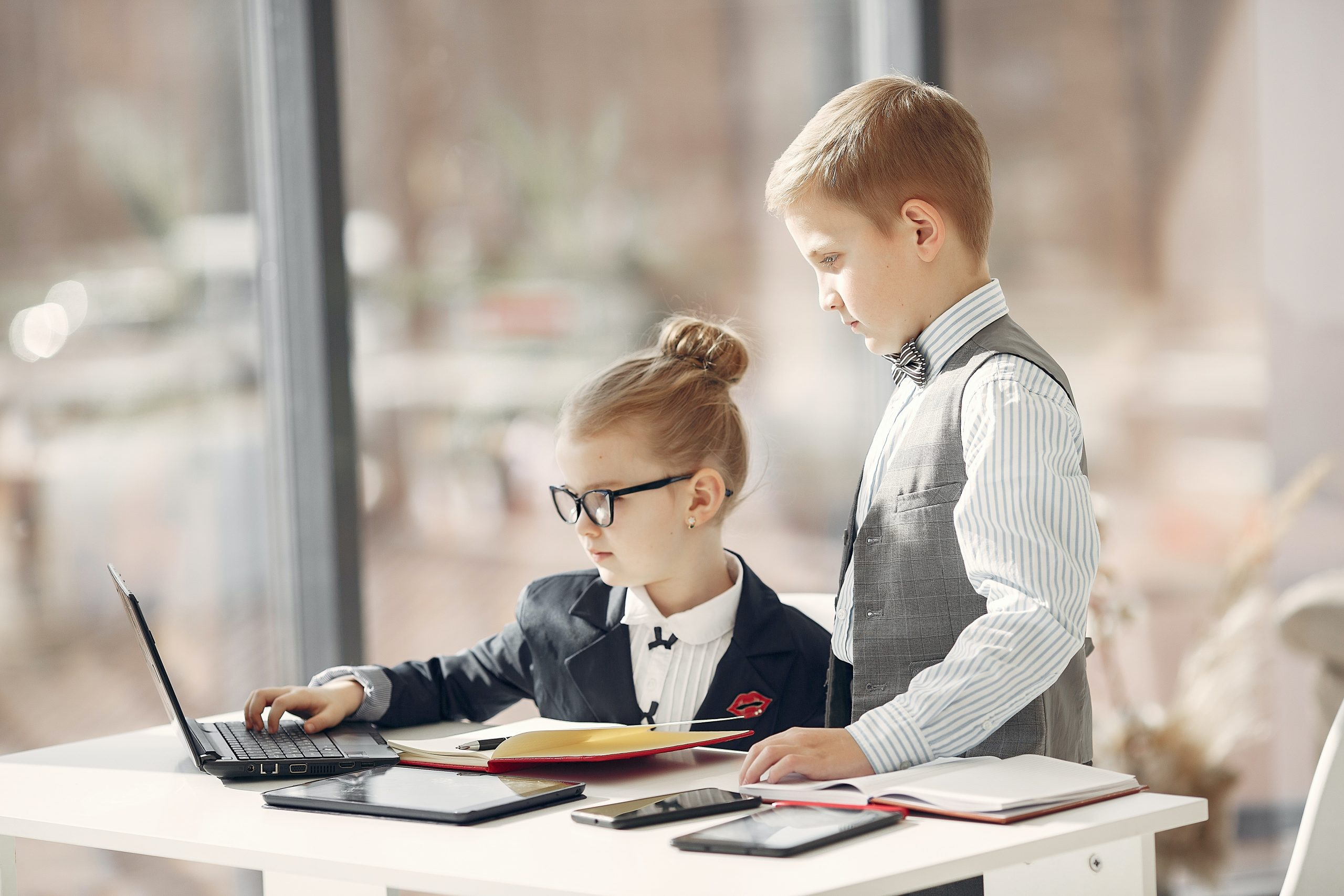 https://www.pexels.com/photo/cute-business-kids-working-on-project-together-surfing-laptop-in-light-workplace-3874121/